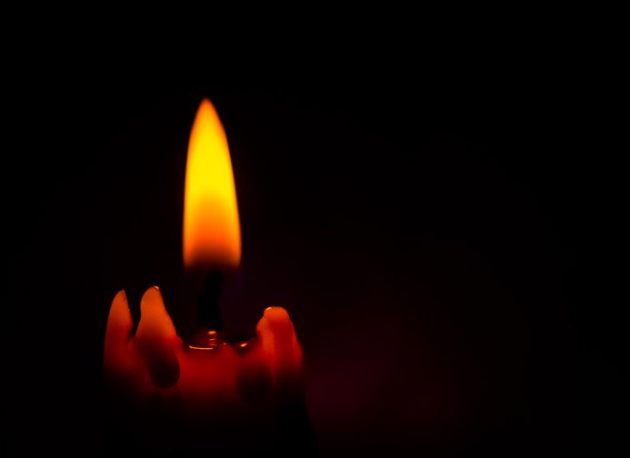 Lighted Candle with Black Background.