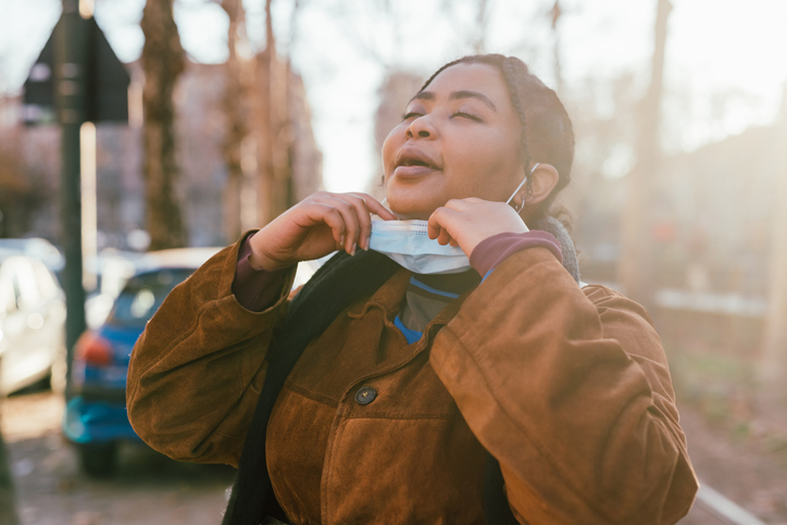 Young woman removing face mask outdoors